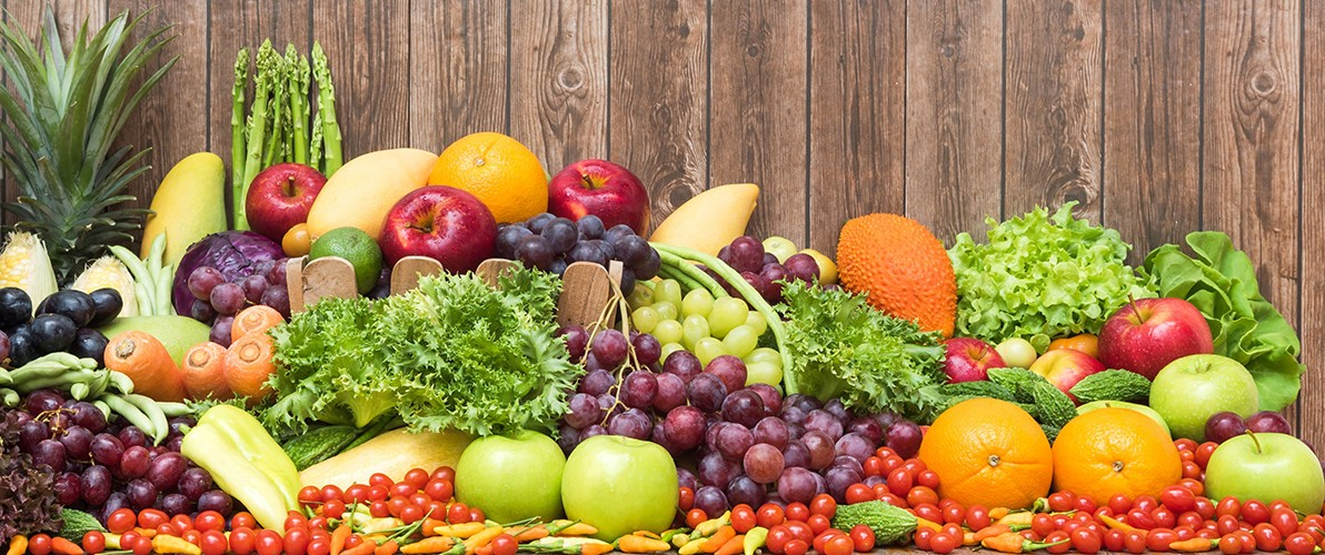 products - large mix of fruit and veg on a wooden background
